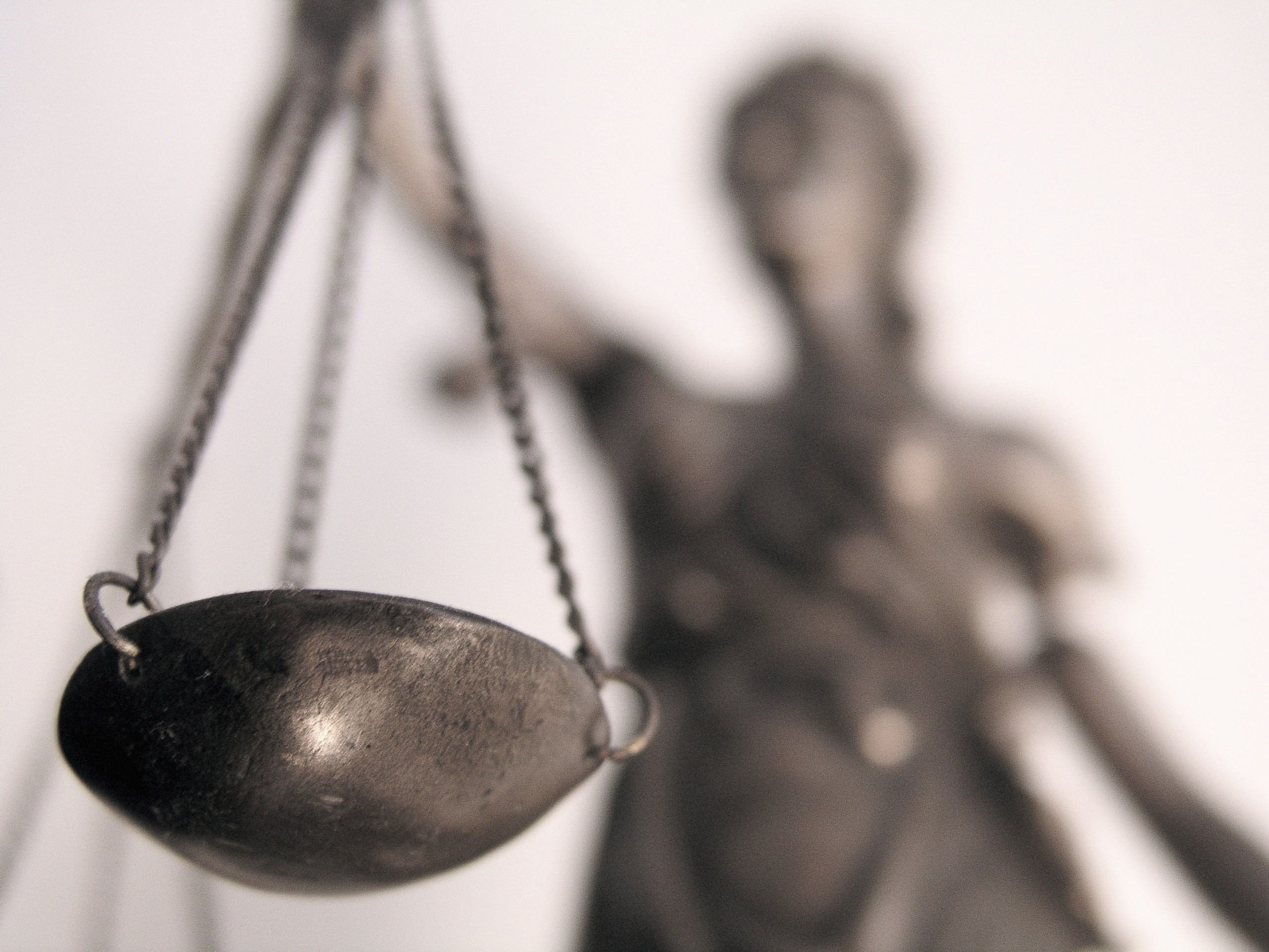 Das Foto zeigt eine Waagschale einer Justitia, dem Sinnbild für Recht und Gerechtigkeit, die Justitia ist im Hintergrund verschwommen und unscharf zu erkennen.