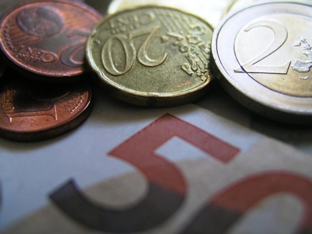 Das Foto zeigt Geldmünzen, die auf einem Geldschein liegen.