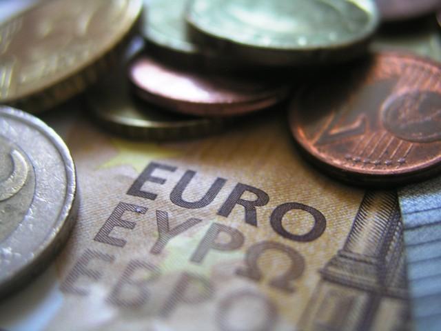 Das Foto zeige Geldmünzen, die auf einem Geldschein liegen.