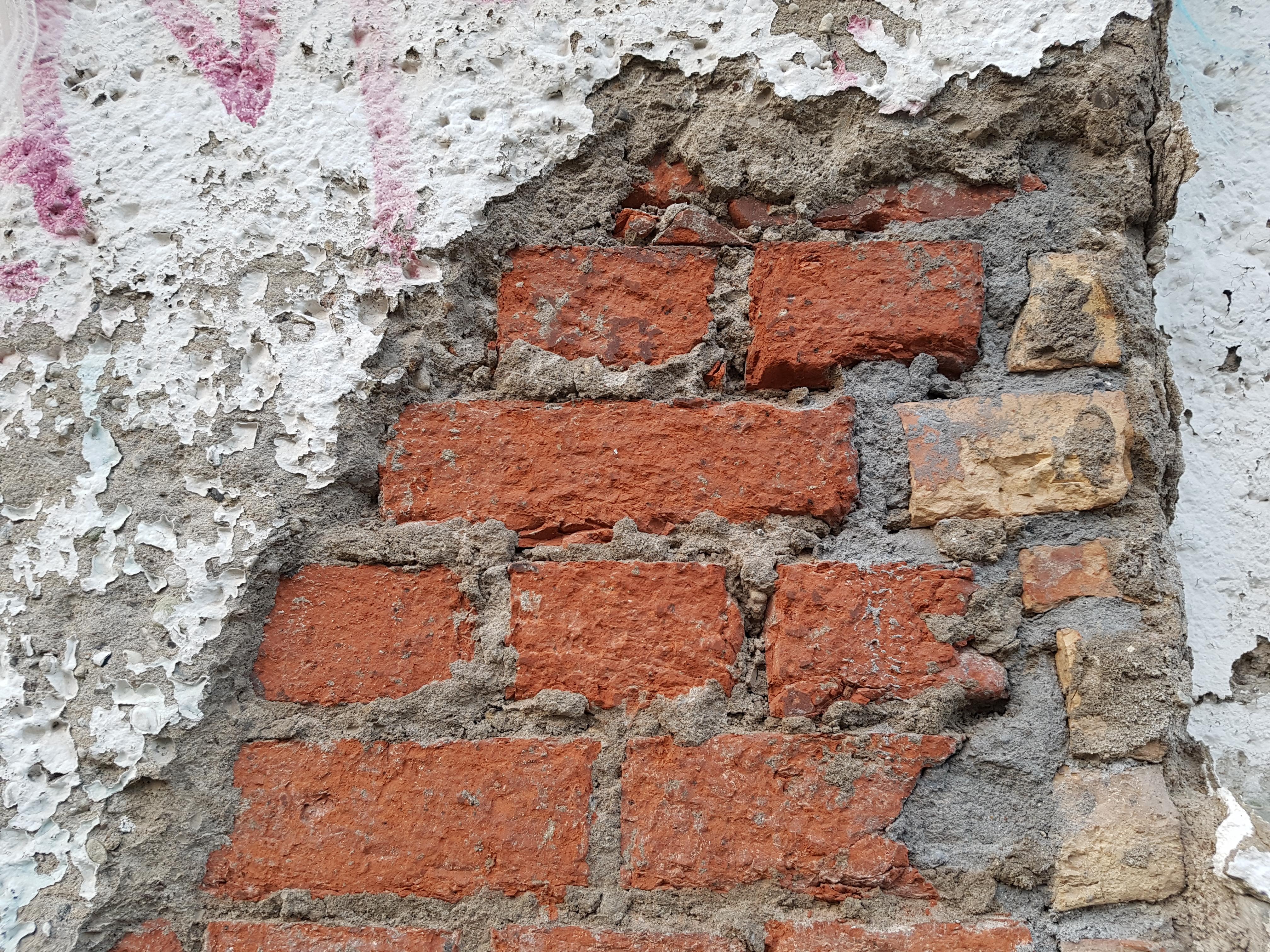 Auf dem Foto ist eine gemauerte Wand zu sehen, die teilweise verputzt und es relativ sanierungsbedürftig aussieht.