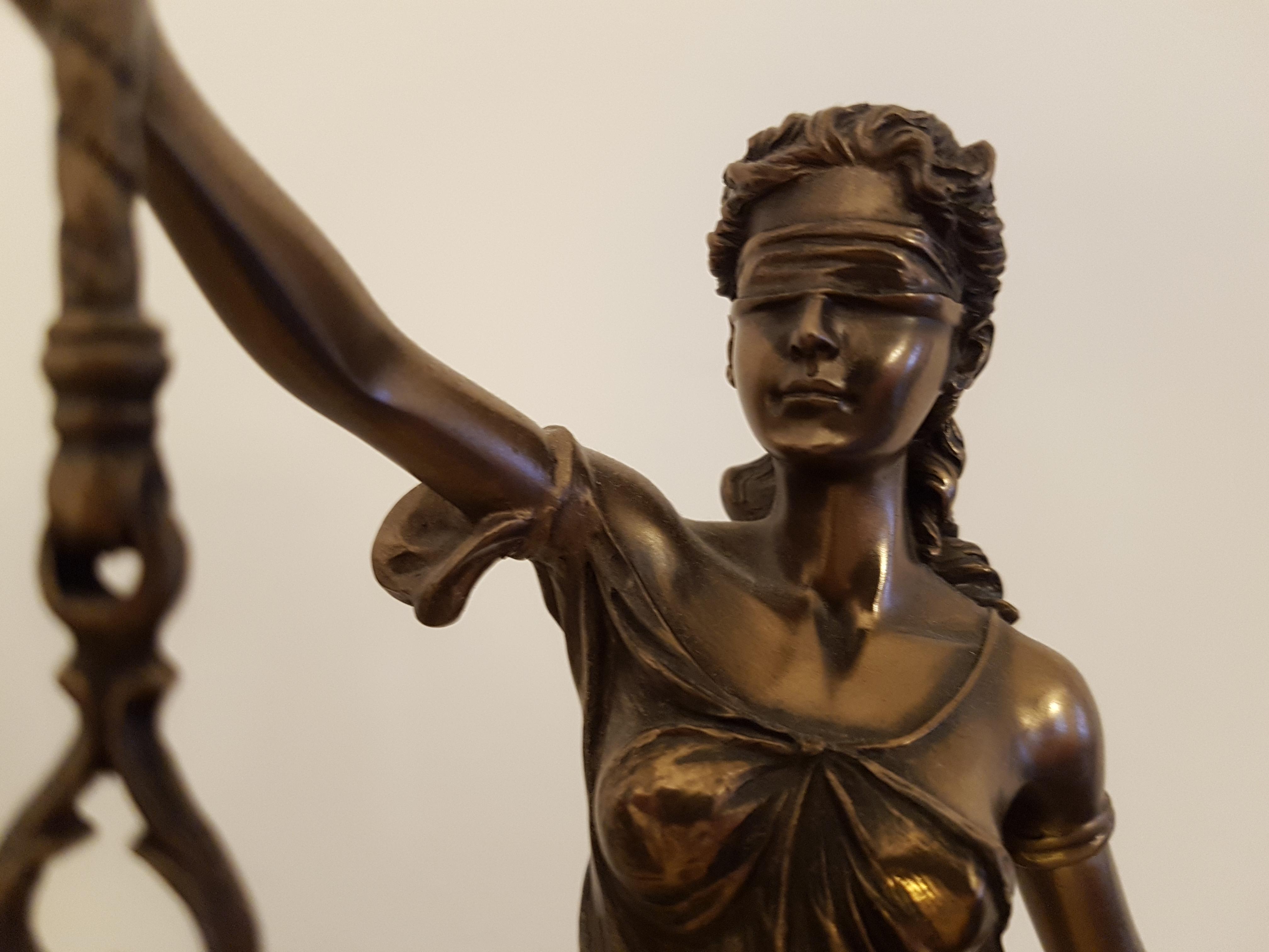 Das Foto zeigt das Sinnbild von Recht und Gerechtigkeit, die Justitia. Zu erkennen ist das Gesicht und der ausgestreckt Arm, der die Waage hält.
