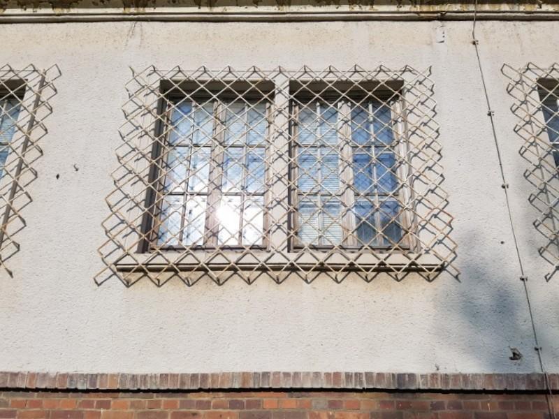 Das Foto zeigt ein vergittertes Fenster.
