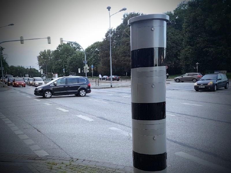Das Foto zeigt ein stationäres Blitzgerät, im Hintergrund Straßenverkehr.