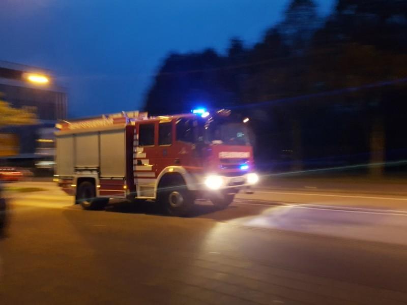 Das Foto zeigt ein im Einsatz befindliches Feuerwehrauto, welches im Dunkeln mit Blaulicht unterwegs ist.