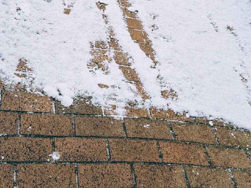 Das Foto zeigt Schnee auf einem Gehweg.