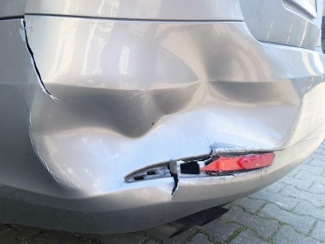 Das Foto zeigt die hintere Stoßstange eines silbergrauen Autos, die an der Ecke stark eingedrückt ist. Unter der Keller befindet sich ein Leuchtelement, welches zur Hälfte zerstört ist.