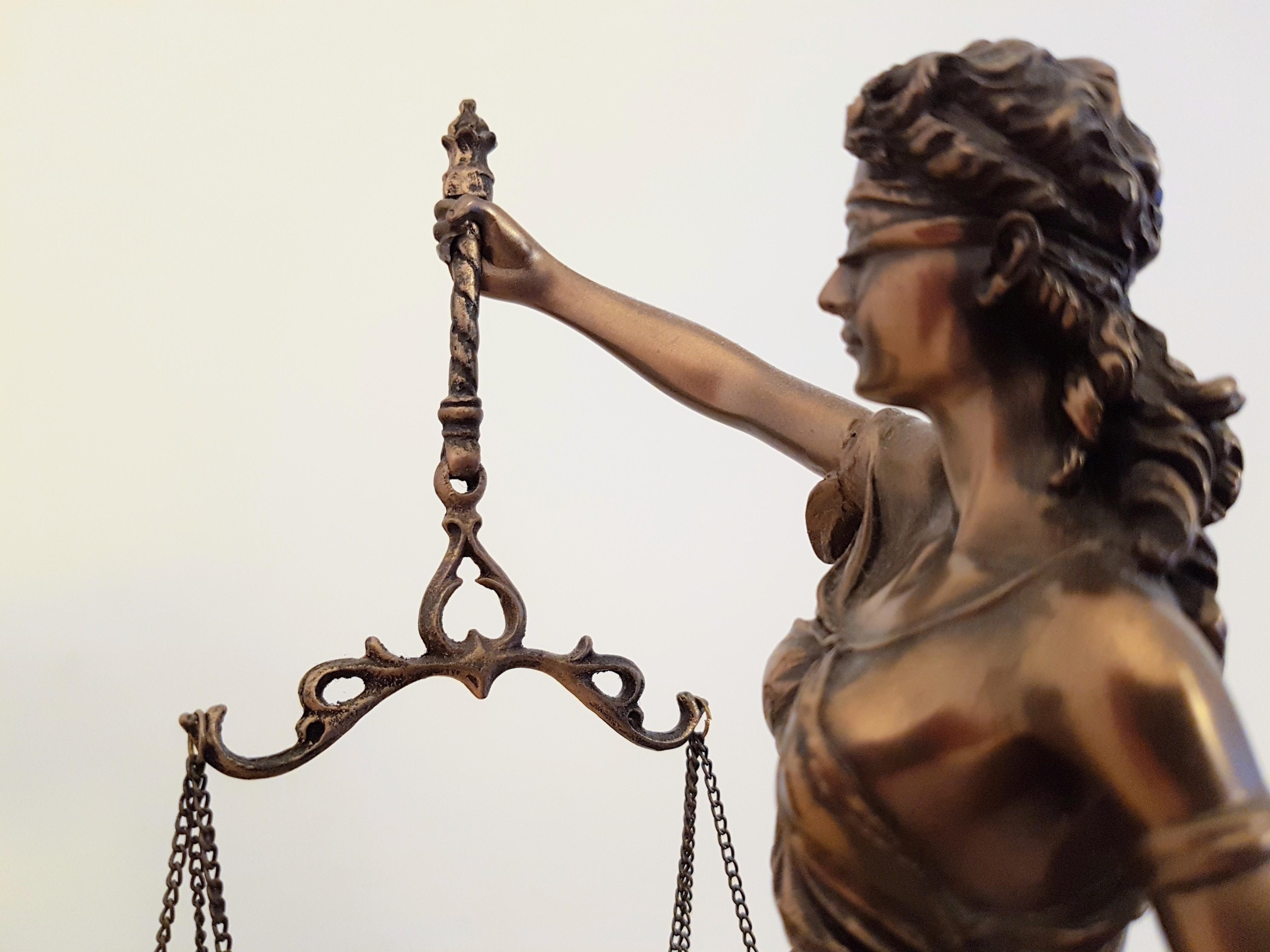 Das Foto zeigt eine Justitia, die in der rechten Hand eine Waage hält, die nur zum Teil zu sehen ist.