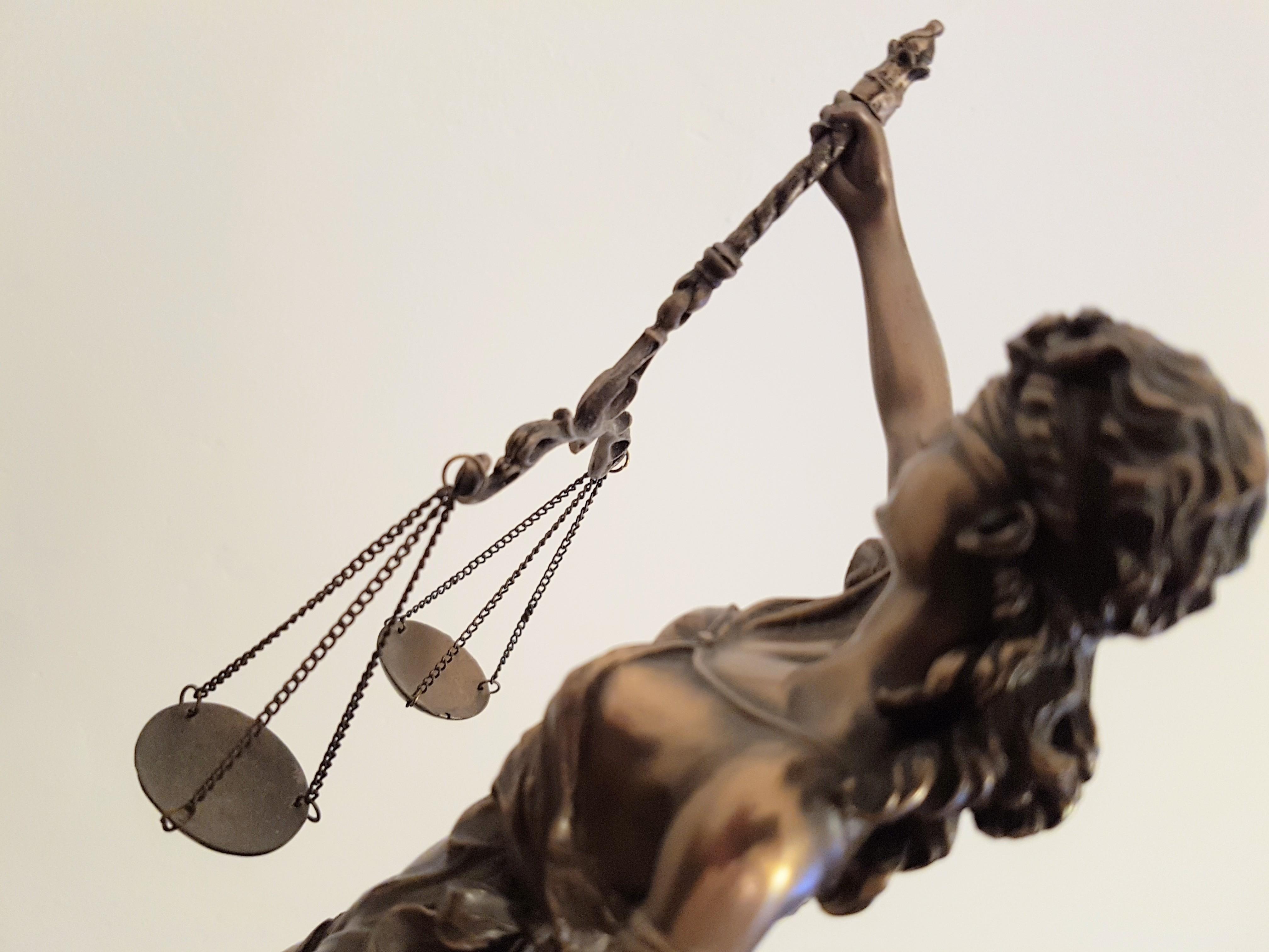 Das Foto zeigt eine von oben fotografierte Justiziar, bei der der rechte Arm die Waage hält.