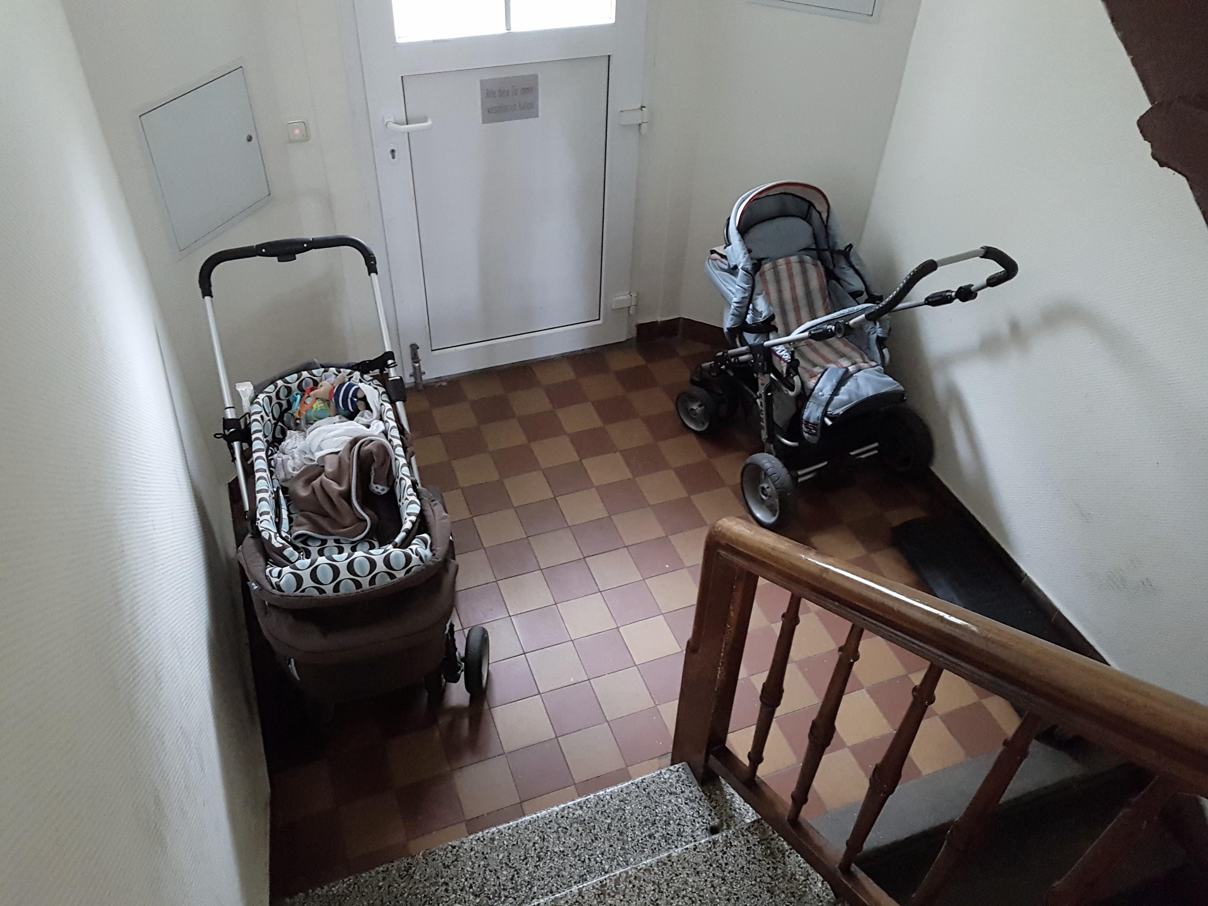 Auf dem Foto ist der Blick in einen Hausflur zu erkennen, links und rechts der Tür stehen jeweils Kinderwagen.