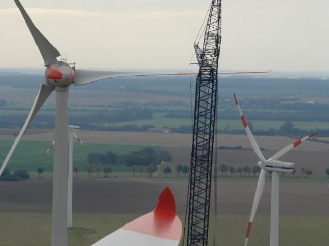Das Foto zeigt einen Teil eines Rotorblattes einer Windkraftanlage sowie zwei Windkraftanlagen und einen Baukran.