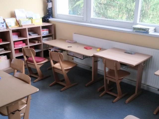 Das Foto zeigt den Blick in ein Klassenzimmer, in dem Tische und Stühle zu sehen sind sowie Regale mit Lehrmaterial.