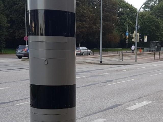 Auf dem Foto ist ein stationäres Blitzgerät zu erkennen, im Hintergrund Straßenverkehr.