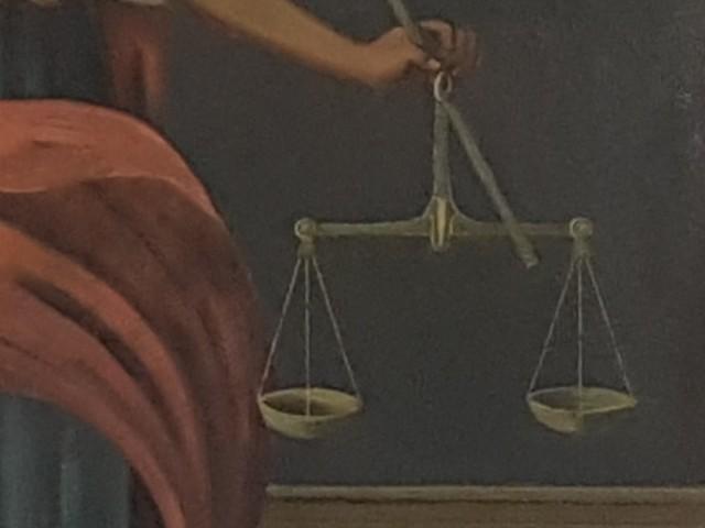 Zu sehen ist eine Waage, fotografiert aus einem Gemälde einer Justiziar, dem Sinnbild für Recht und Gerechtigkeit.