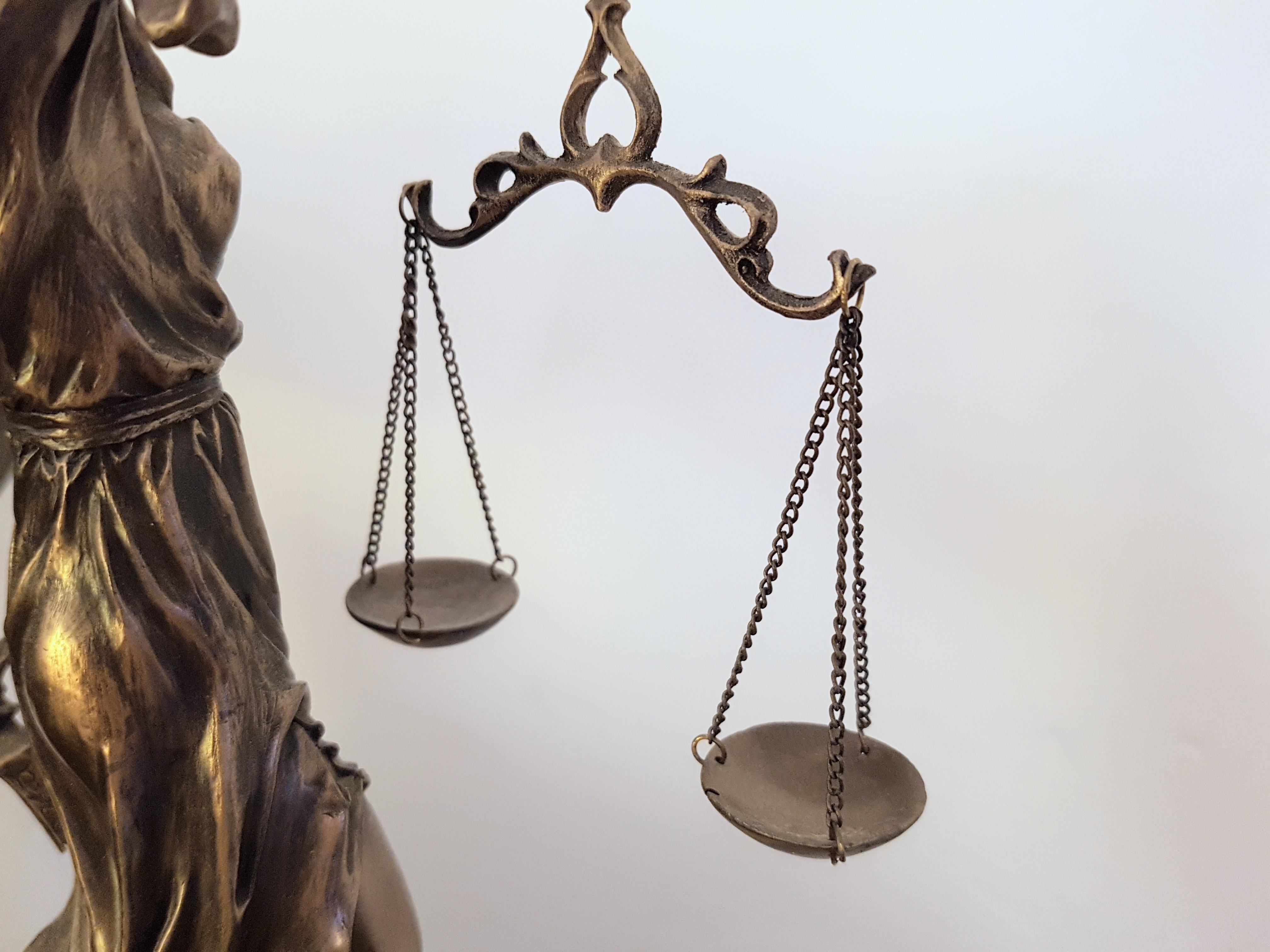 Zu sehen ist teilweise eine Justiziar, das Sinnbild von Recht und Gerechtigkeit, sowie die von ihr gehaltene Waage.