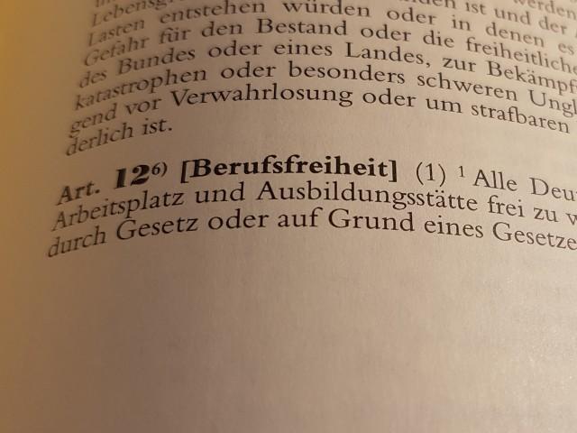 Das Foto zeigt den Blick in das Gesetzbuch, hier das Grundgesetz mit dem aufgeschlagenen Artikel 12 Berufsfreiheit.