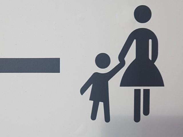 Das Foto zeigt eine Mutter mit einem Kind, welches sie an der Hand hält. Die Figuren sind auf weißem Grund stilisiert dargestellt, links befindet sich ungefähr in der Bildmitte ein horizontal verlaufender schwarzer Balken.