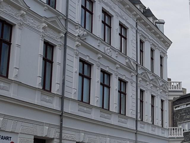 Das Foto zeigt die Fassade eines Wohnhauses mit mehreren Fenstern und Verzierungen an der Fassade.