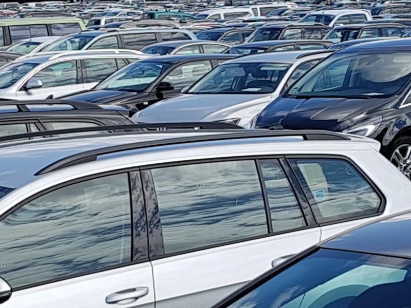 Das Foto zeigt zahlreiche parkende Fahrzeuge auf einem Parkplatz.