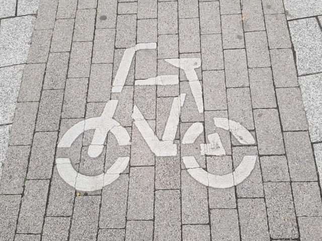 Das Foto zeigt die auf einem Weg angebrachte Markierung in Gestalt eines Fahrrades.