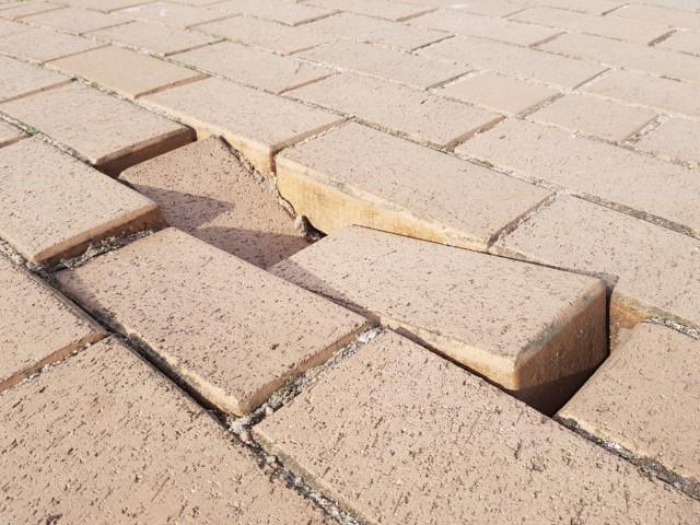 Das Foto zeigt einen defekten Gehwege, bei dem einzelne Steine stark abgesenkt hat.