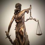 Das Foto zeigt einen von hinten fotografierte Justitia, welche Recht und Gerechtigkeit symbolisiert, das ist zu erkennen, dass sie in der rechten Hand die Waage und in der linken Hand ein Schwert hält.