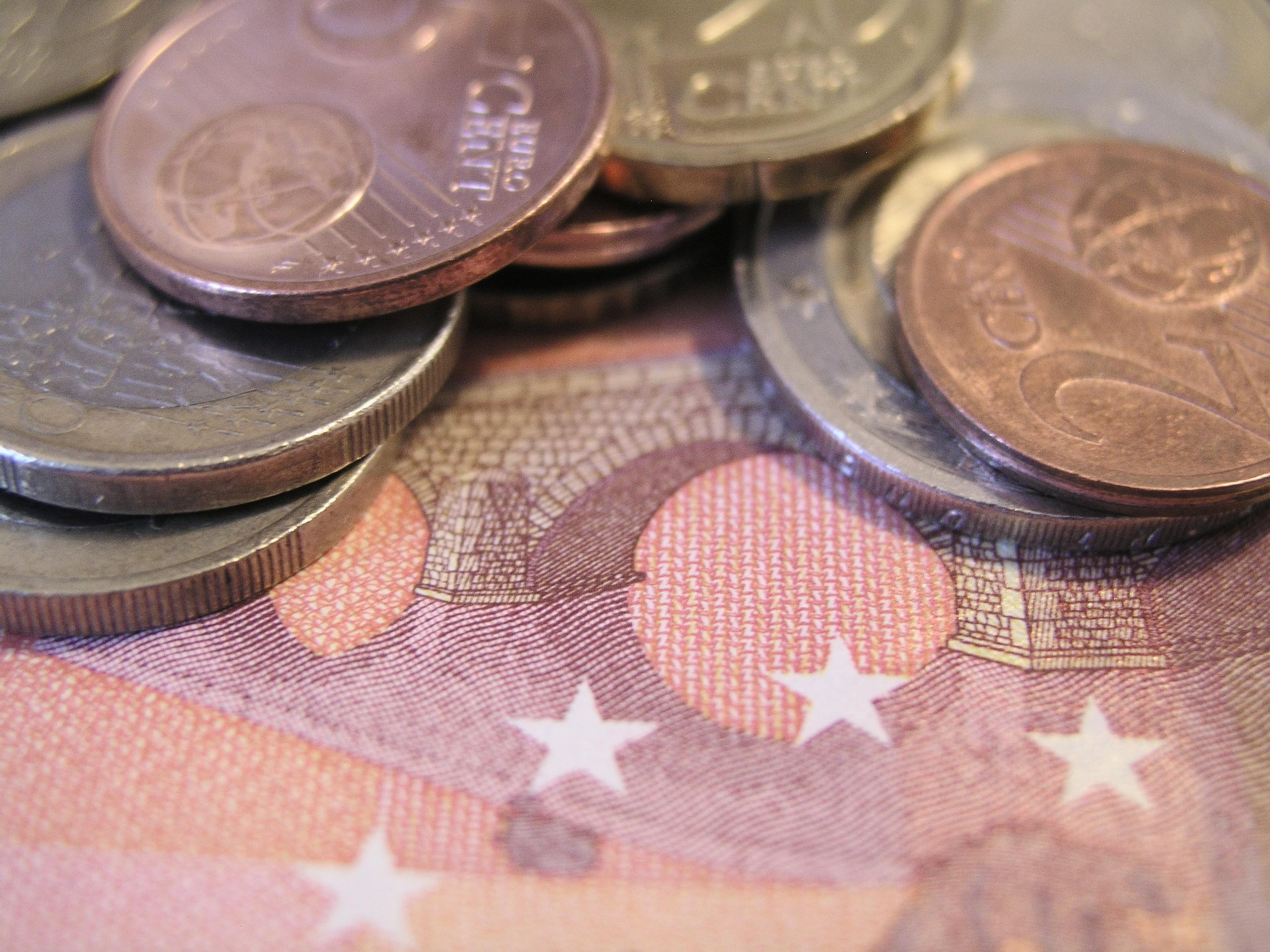 Das Foto zeigt den Ausschnitt eines Geldscheines, auf dem Münzen liegen.