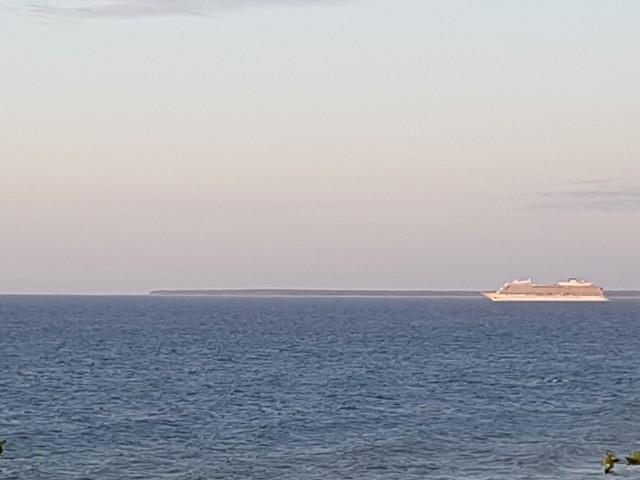 Das Foto zeigt den Blick auf See mit einem Kreuzfahrtschiff.