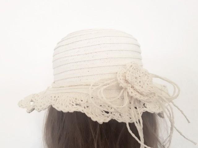 Das Foto zeigt eine Person von hinten mit einem weißen Hut.