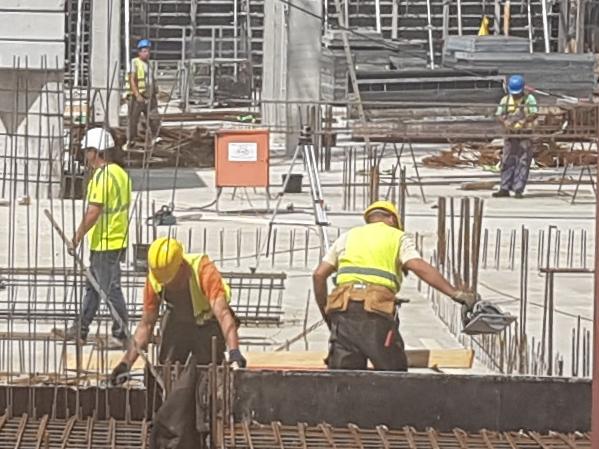 Auf dem Foto ist eine Baustelle mit mehreren Bauarbeitern zu sehen.