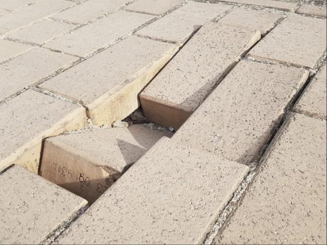 Das Foto zeigt einen Gehweg, bei dem einzelne Steine derart abgesenkt sind, dass Fußgänger zu stürzen drohen.