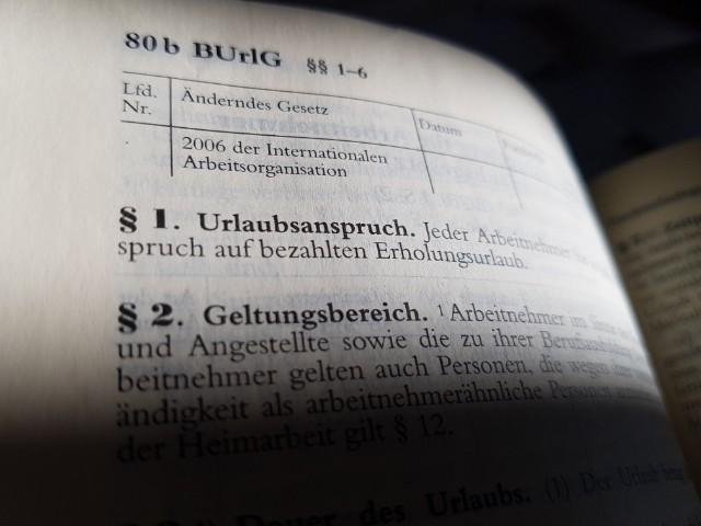 Das Foto zeigt den Blick in ein aufgeschlagenes Gesetzbuch, es ist zu erkennen Paragraph 1 Urlaubsanspruch.