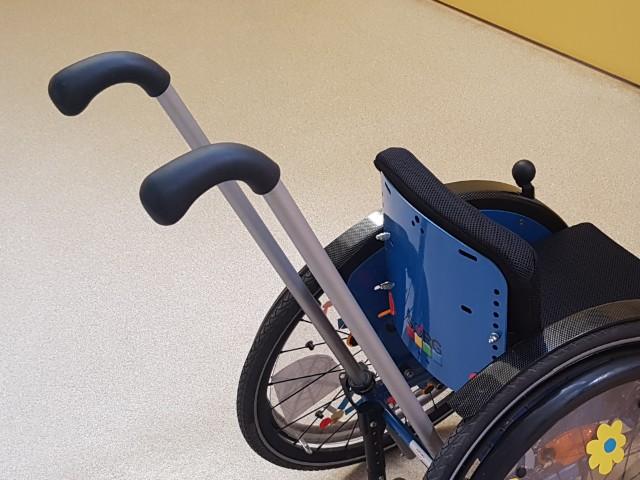 Auf dem Foto ist ein Rollstuhl zu erkennen mit zwei großen Griffen zum schieben.