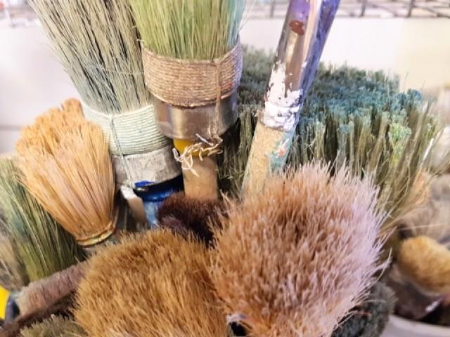 Das Foto zeigt zahlreiche gebrauchte Pinsel, Blick auf die Borsten.