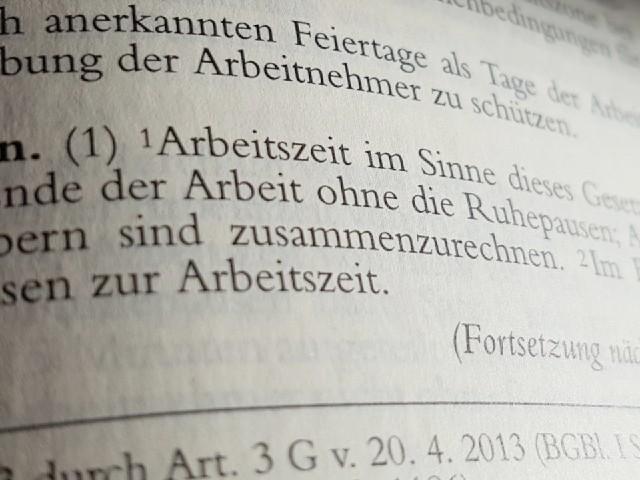 Das Foto zeigt den Blick in ein aufgeschlagenes Gesetzbuch, in dem das Wort Arbeitszeit zu sehen ist.