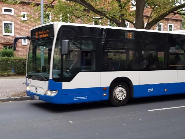 Zu sehen ist das vordere Drittel eines Nahverkehrsbusses, der unten blau und sonst weiß ist.