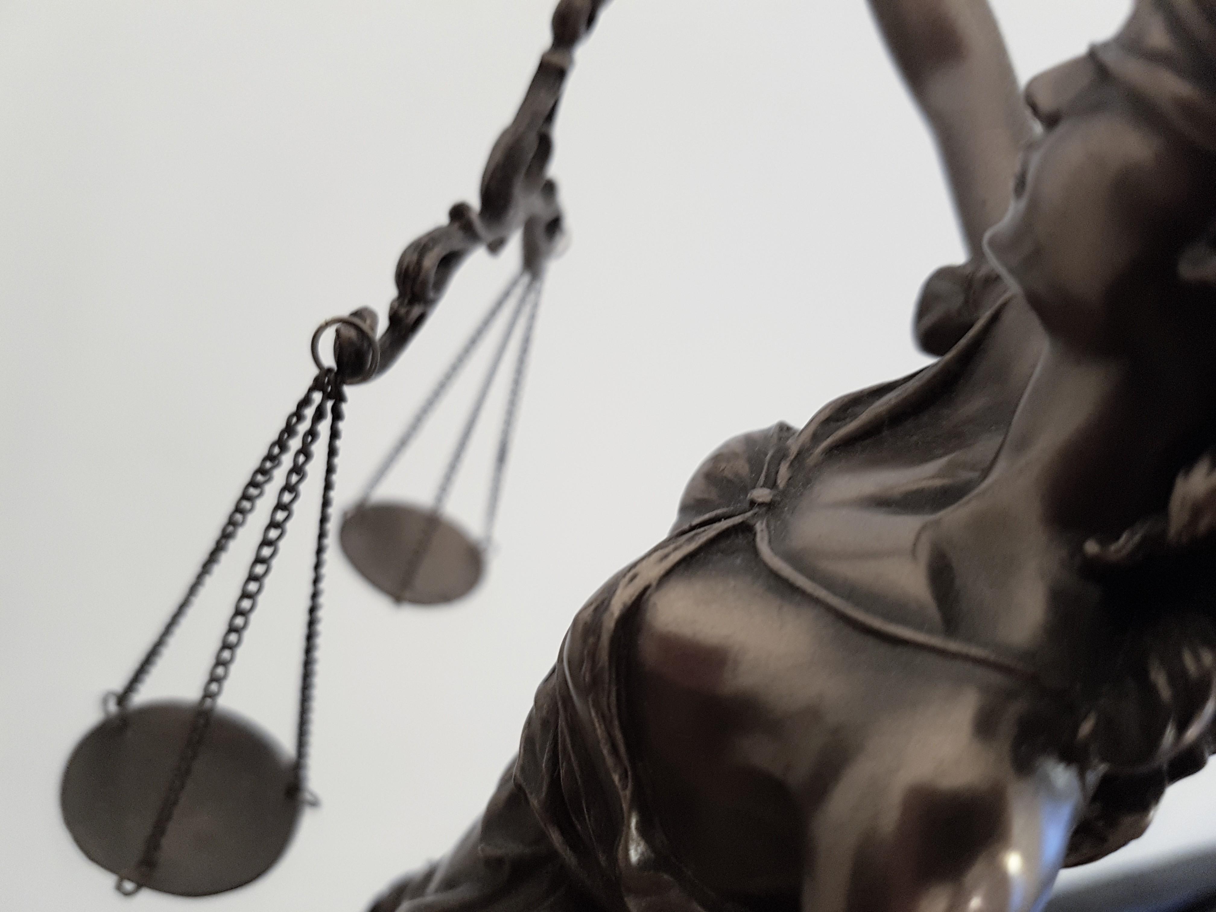 Das Foto zeigt Justitia, die Symbolfigur der Gerechtigkeit. Die Perspektive ist voll schräg oben gewählt, sodass man das Gesicht, den Brustbereich und die Waage erkennen kann.