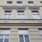 Zu sehen ist eine ocker-gelbe mit Schmuckelementen verzierte Hausfassade von unten fotografiert mit Fenstern.