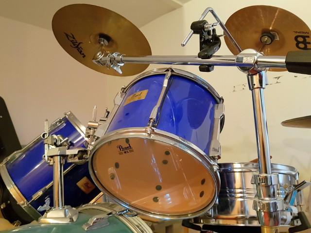 Auf dem Bild ist ein Schlagzeug zu erkennen mit mehreren Elementen, u. a. zwei blauen Trommeln, zwei Schellen und Halterungs-Gestänge.