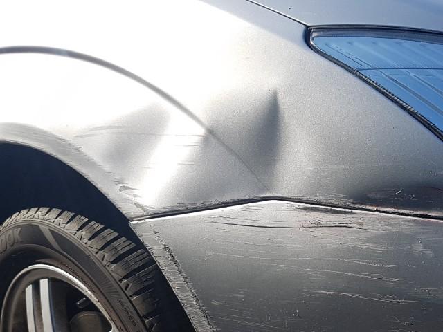 Das Foto zeigt ein silberfarbenden vorderen Kotflügel eines Autos, an dem eine deutliche Delle und Abriebspuren zu erkennen sind.