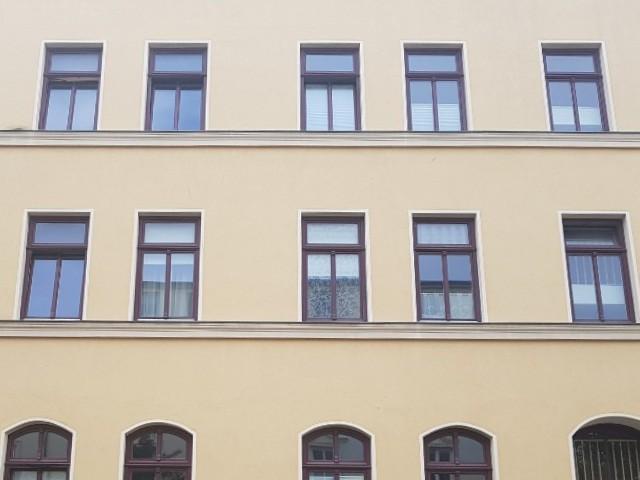 Das Bild zeigt eine Hausfassade in gelber Farbe mit dunkel gerahmten Fenstern.