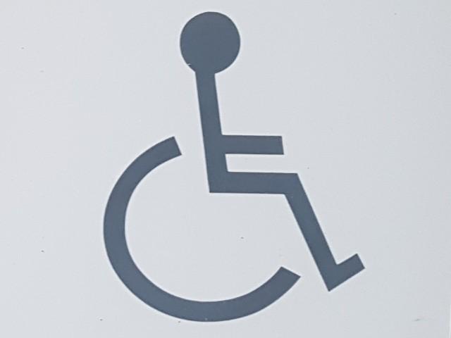 Das Foto zeigt das Symbol eines Rollstuhlfahrers, stilisiert schwarz auf weißem Grund.
