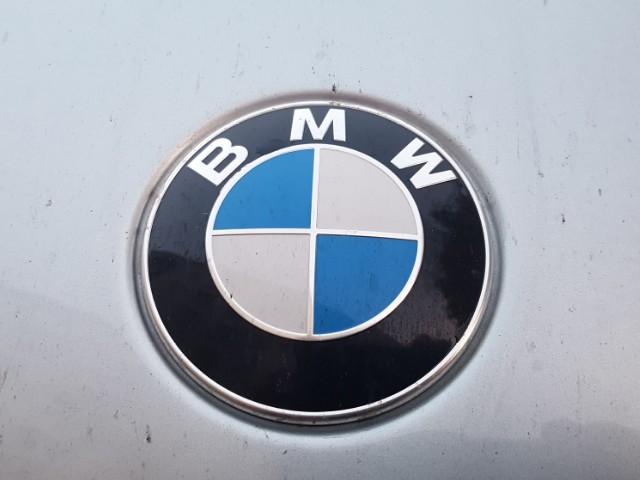 """Zu sehen ist das BMW-Markenzeichen, ein schwarzer Kreis, in dem oben die Großbuchstaben """"BMW"""" stehen, und der einen kleineren geviertelten Kreis umgibt, bei welchem zwei Viertel weiß und zwei blau sind."""