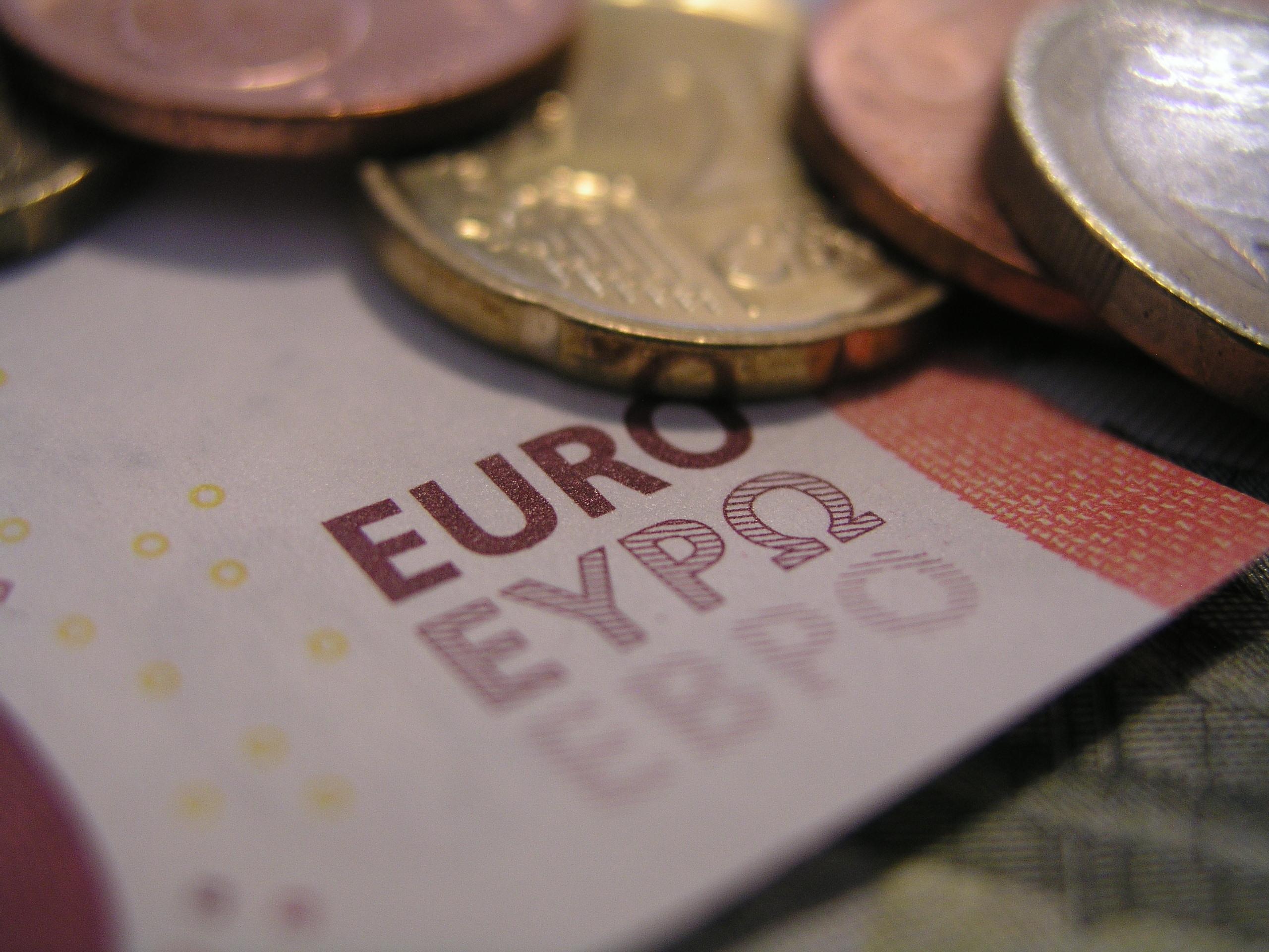Ein Ausschnitt eines 10 Euro Scheins ist zu sehen, auf dem mehrere Münzen liegen.