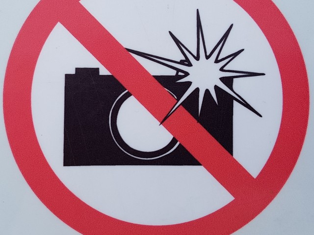 Das Foto zeigt das Piktogramm eines durchgestrichenen Fotoapparats mit stilisiertem Blitzlicht.