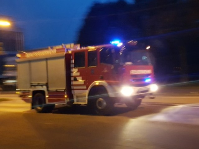 Zu sehen ist ein Feuerwehrauto, welches in der Dämmerung mit Blaulicht zu einem Einsatz unterwegs ist.
