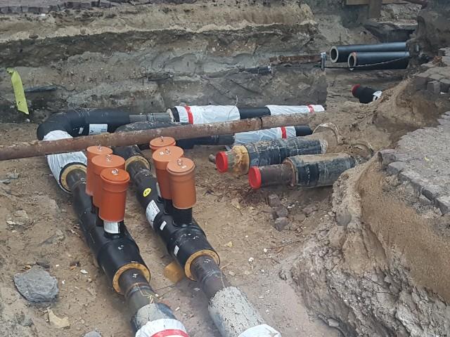 Das Foto zeigt eine Baugrube mit darin befindlichen Rohrleitungen.
